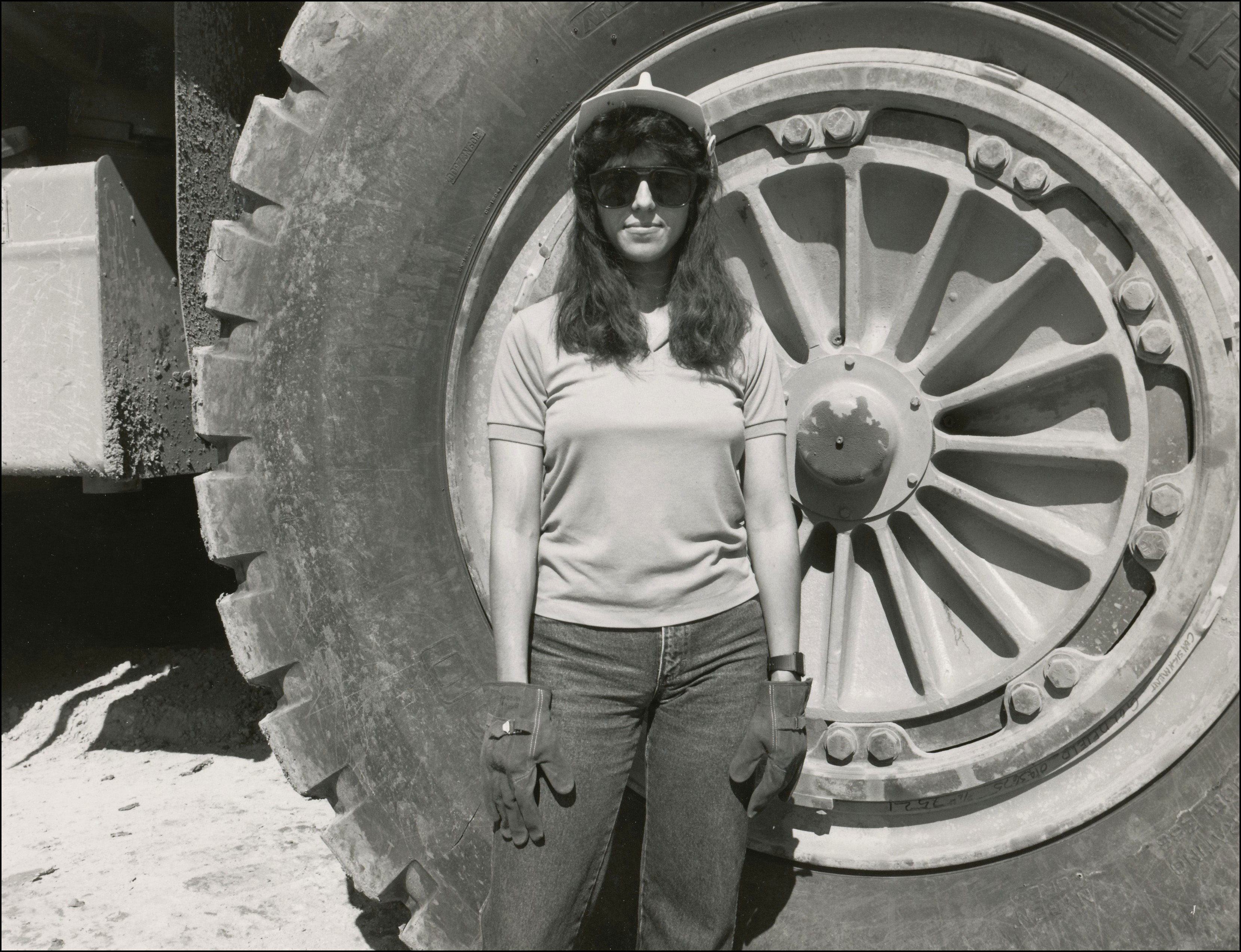 Miner woman standing in front of a very large tire on a piece of construction equipment
