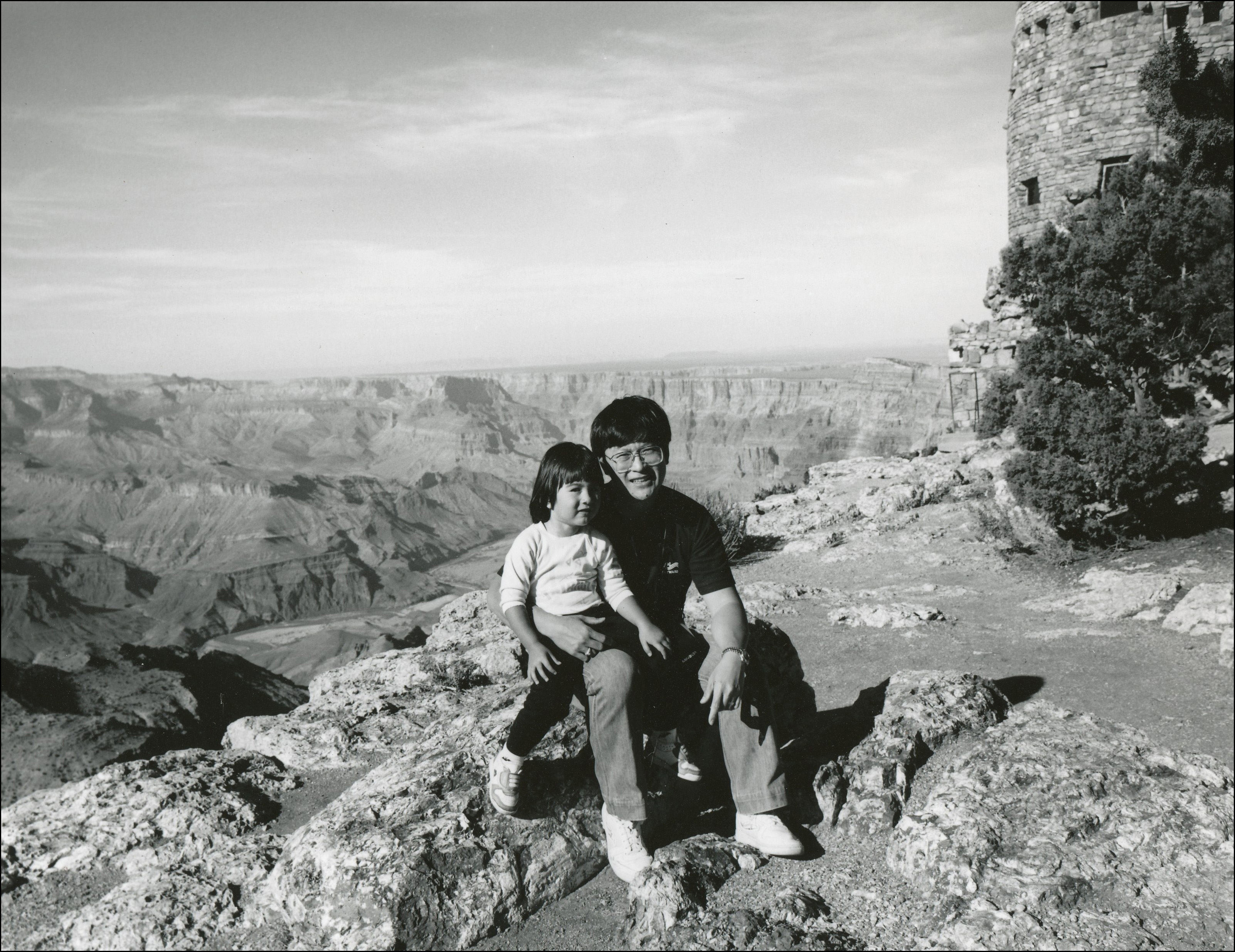 A father and his youg daugher sitting on a rock in front of the Grand Canyon