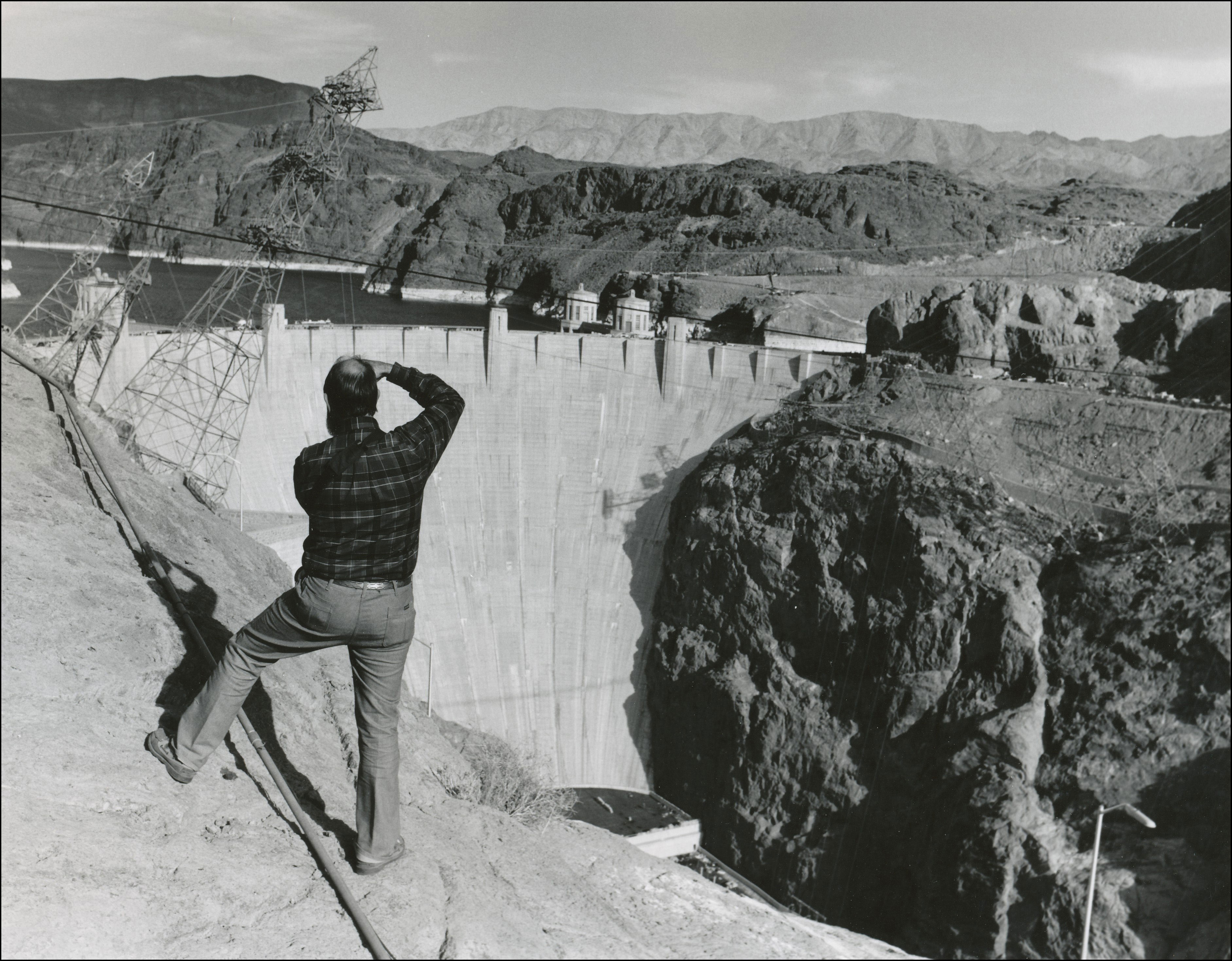 View of the back of a man standing taking a photo of hoover dam. Hoover dam in the background with water behind it.
