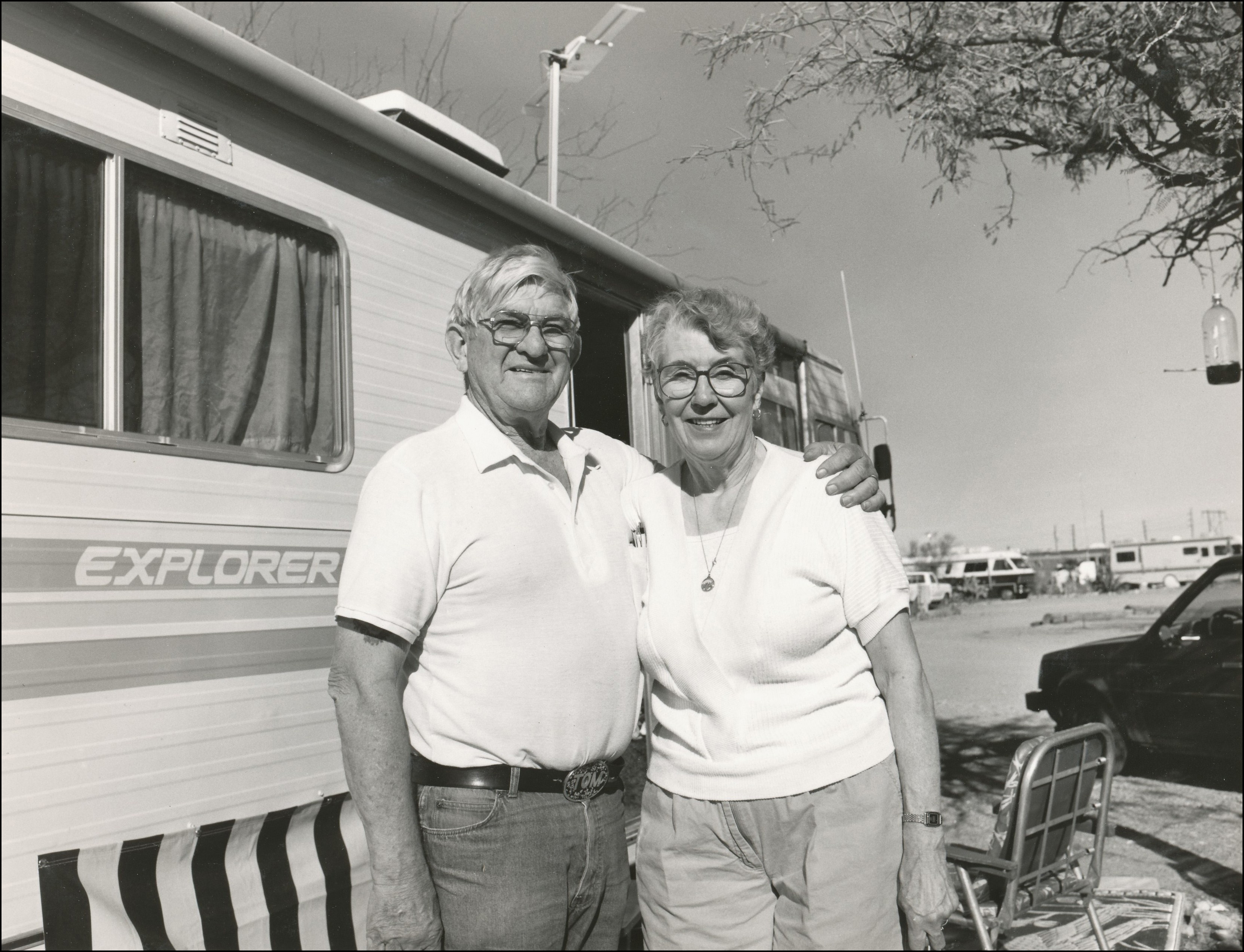 Older couple standing in front of their camper