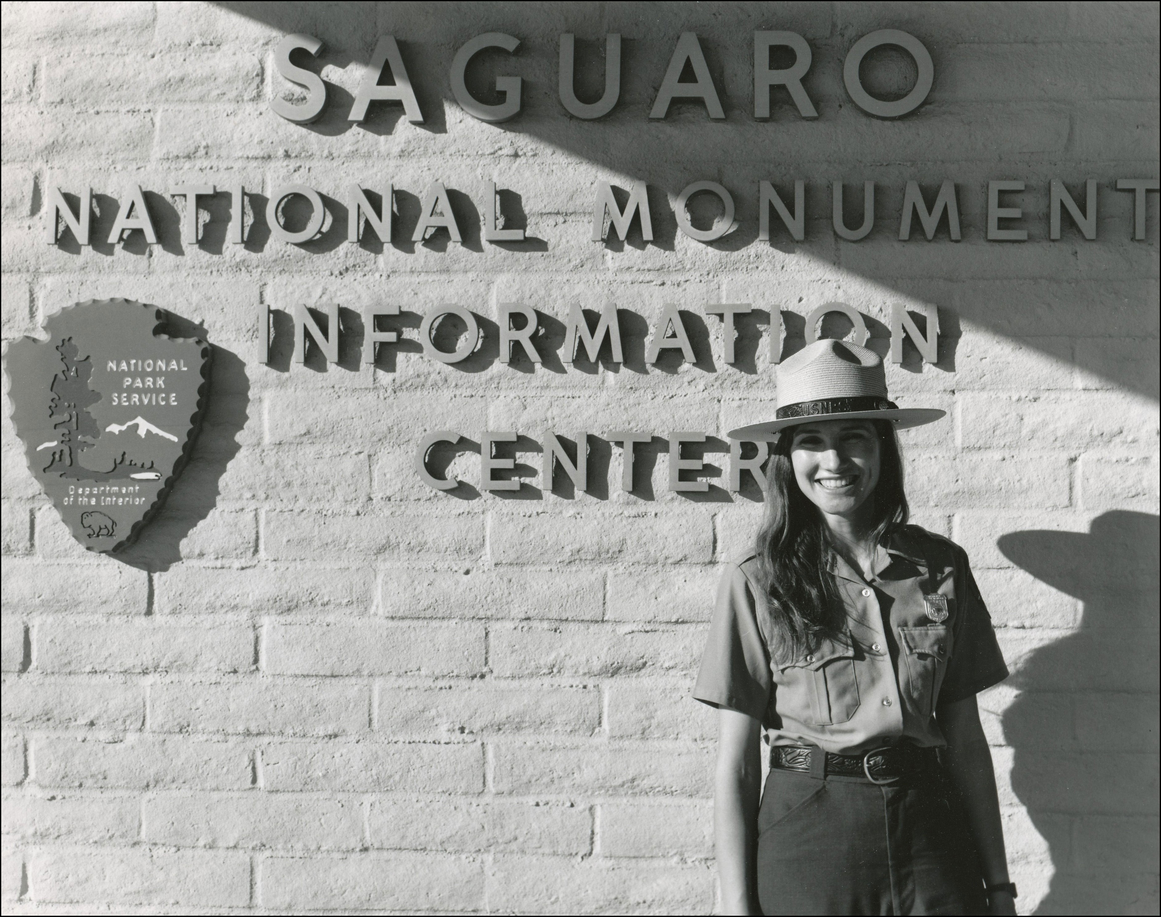 Woman Park ranger in uniform including hat standing in front of building with Naitonal Park Sign