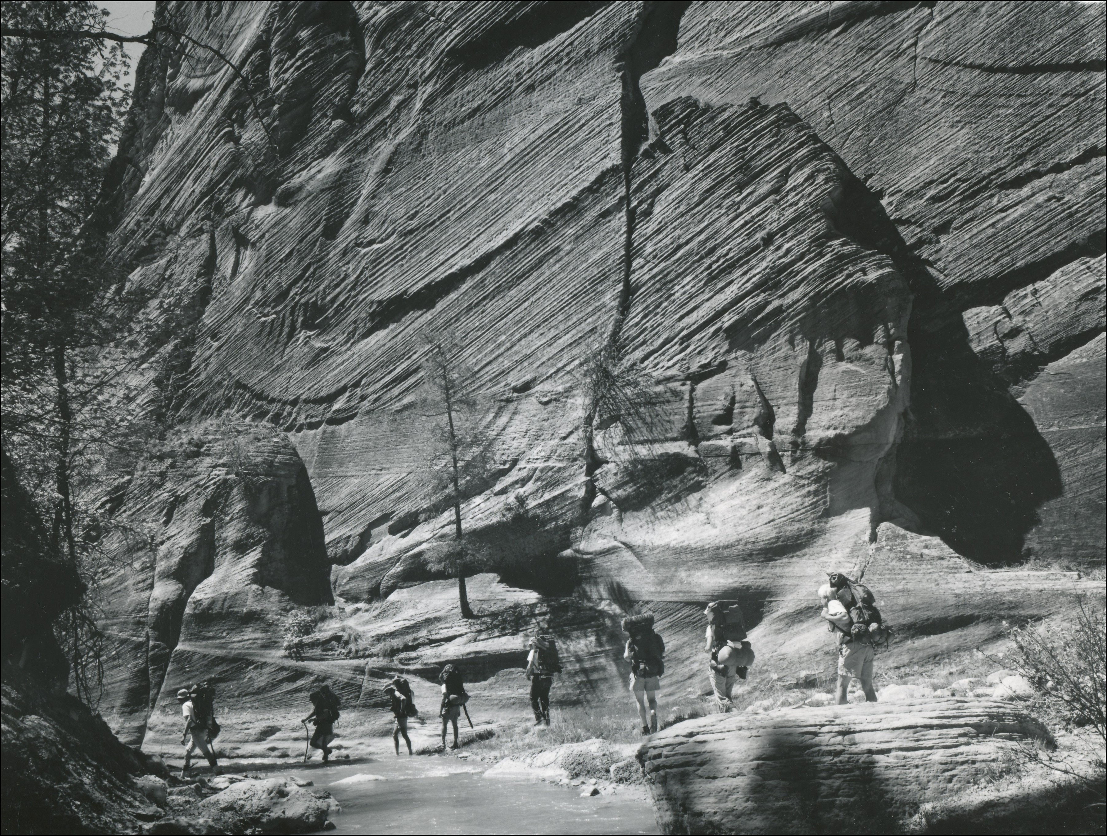 several people walking down a trail in single file at the bottom of tall rock ledges