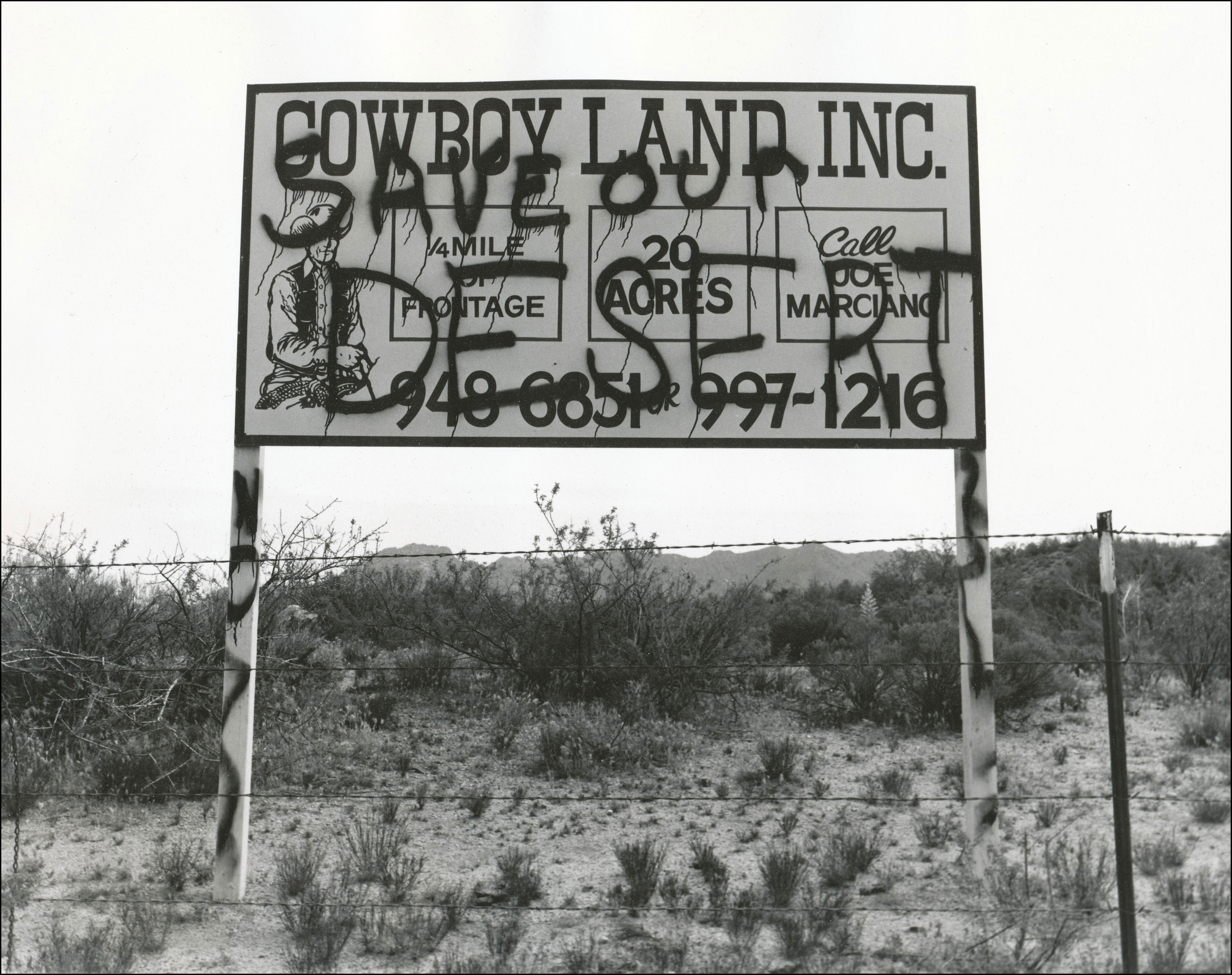 Sign on the side of a road that says Cowboy Land Inc. Quarter mile of frontage, 20 acres, call Joe Marciano, 949-6851, 997-1216. Spray painted over with the words Save our Desert