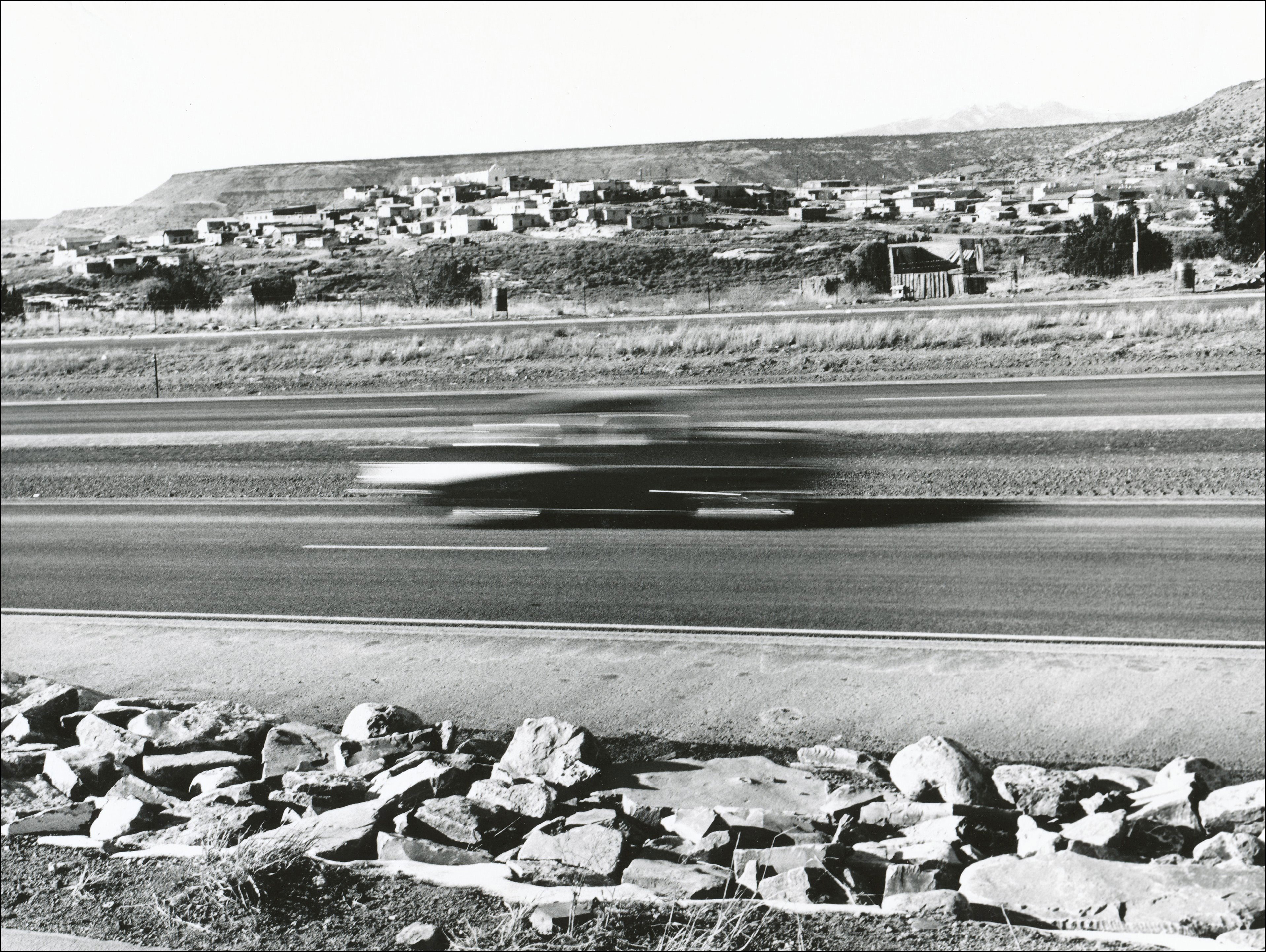 Photo of blurred car on interstate highway with a town on the otherside in the distance, on the very top of the hill is a church, a plateau is behind the town