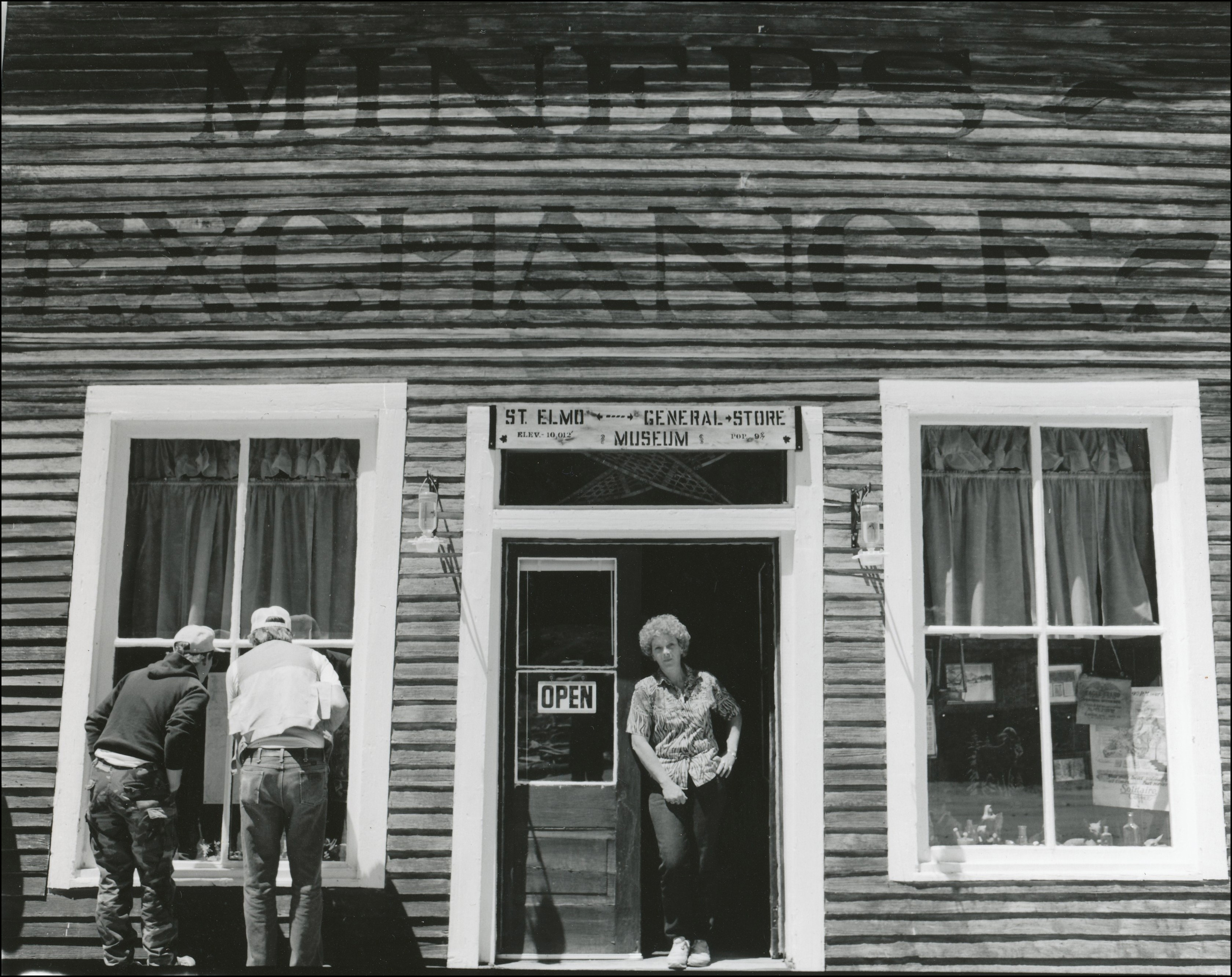 Front view of old general store with woman standing on open door and two men looking in the window