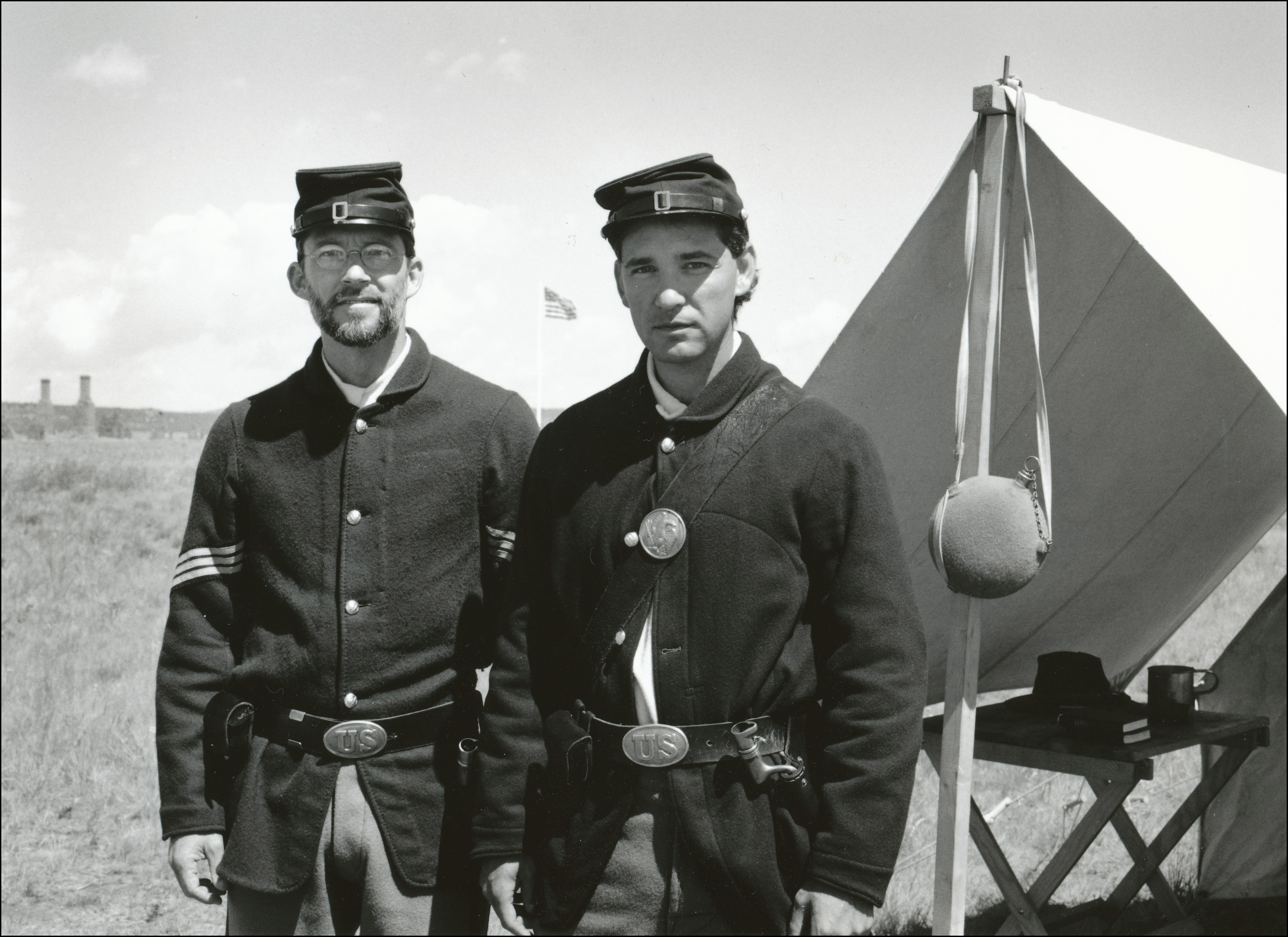 Two men dressed up as soldiers in front of old tent at an old fort