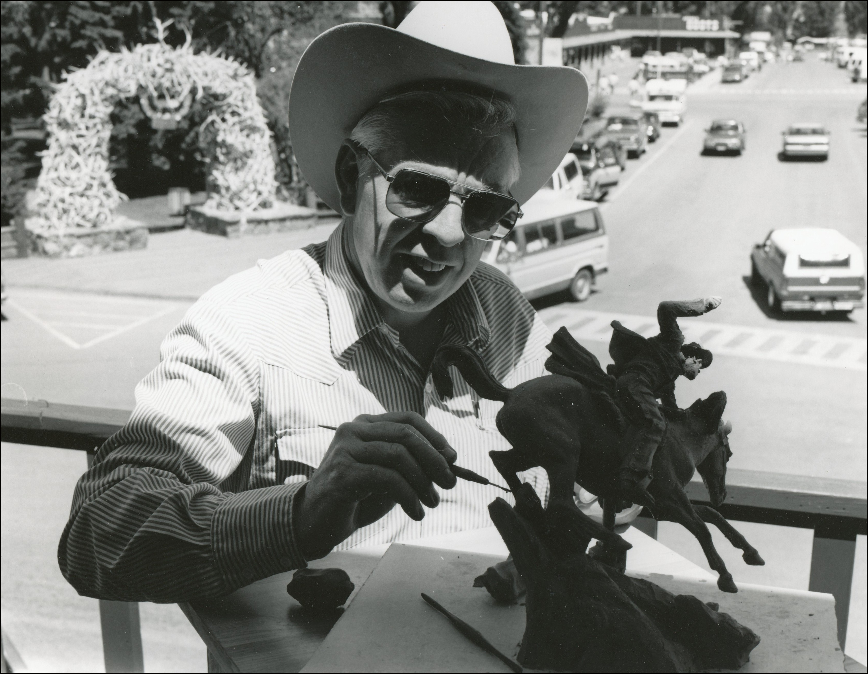 Artist wearing a cowboy hat on balcony working on a sculpture of a man running a horse down a hill