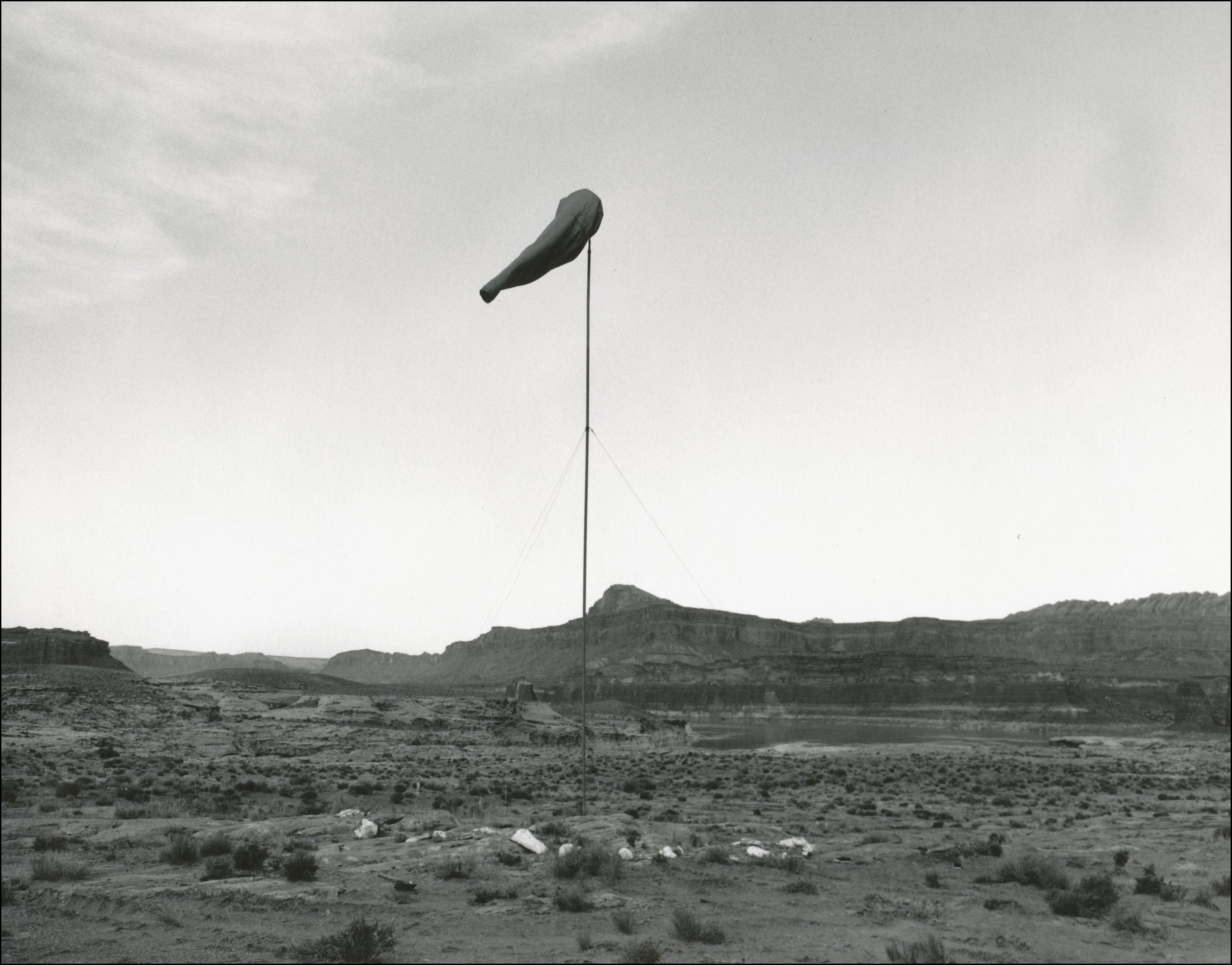 Wind flag in desert with plateaus in background