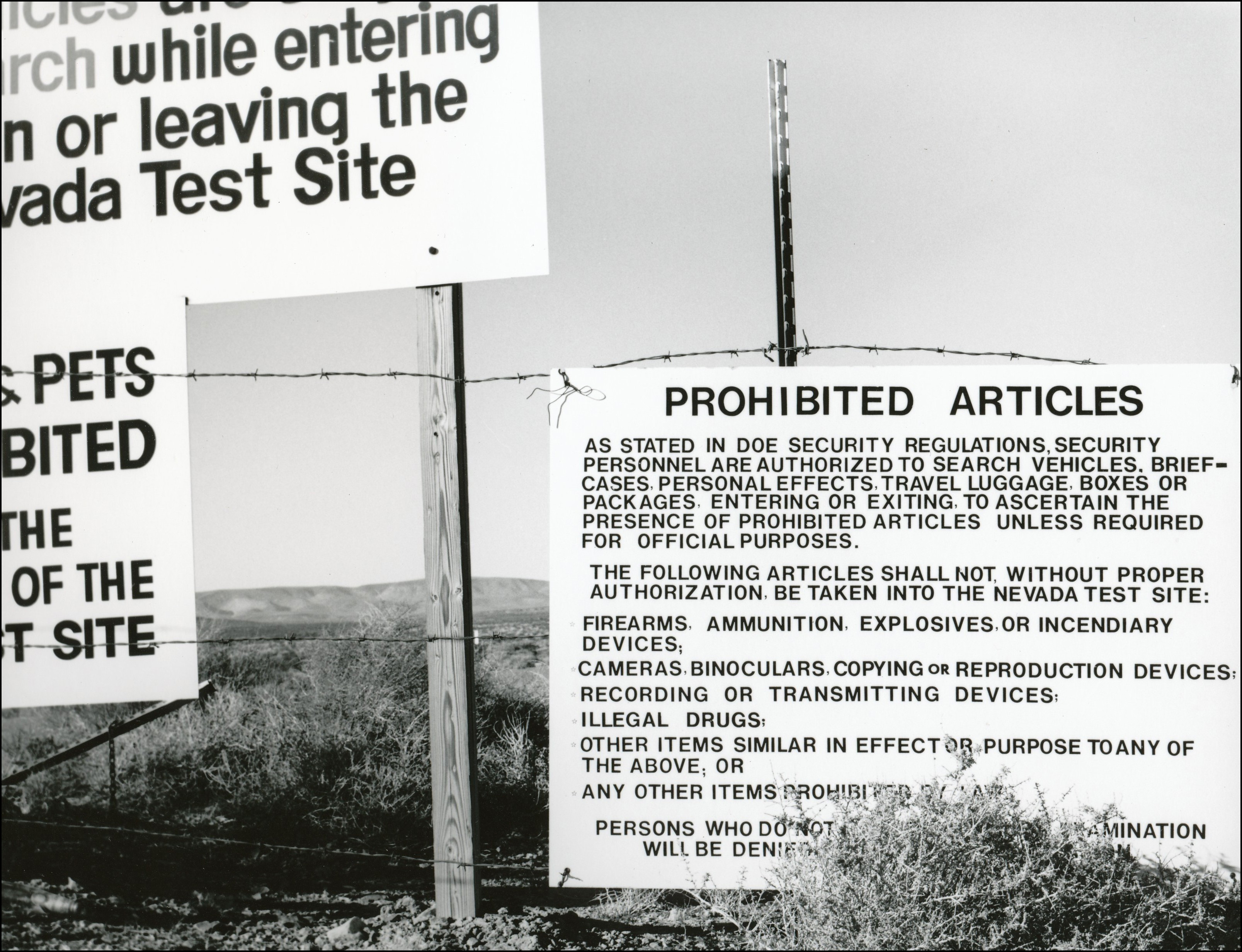 Warning signs for nuclear proving grounds hanging on fence