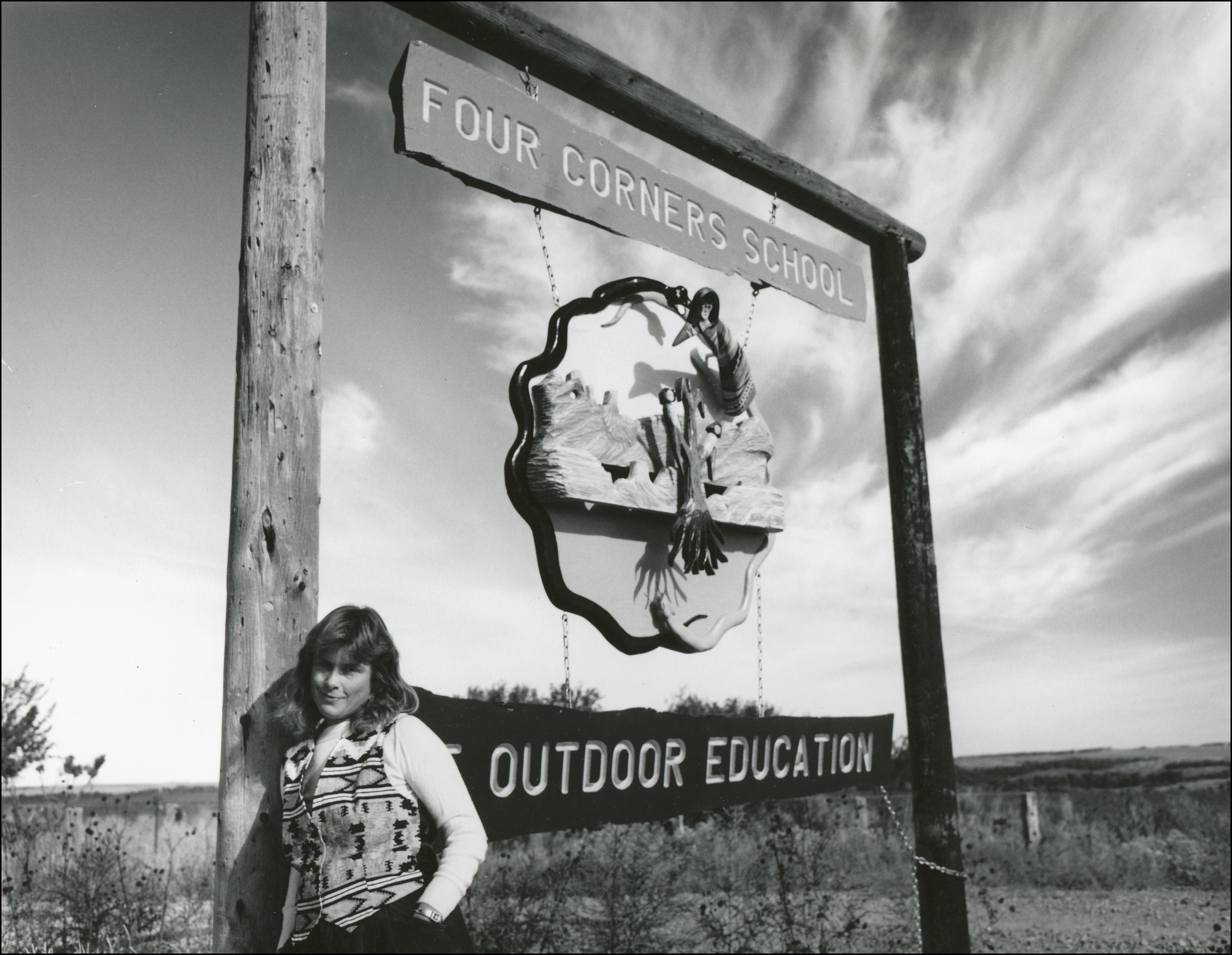 "woman leaning against sign post which says ""Four Corners School and Outdoor Education"""