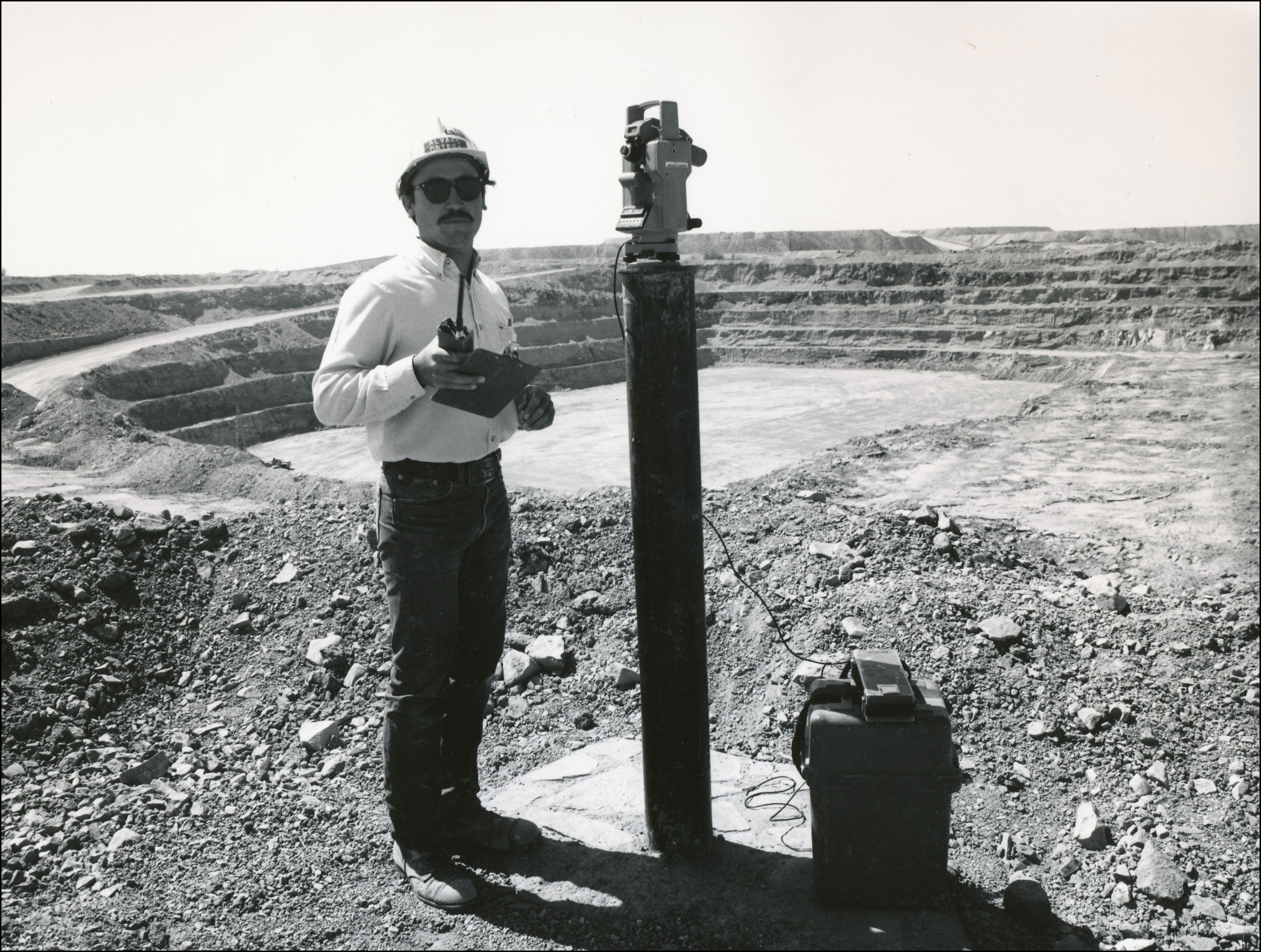 Man in glasses and hard hat standing next to an open mining area