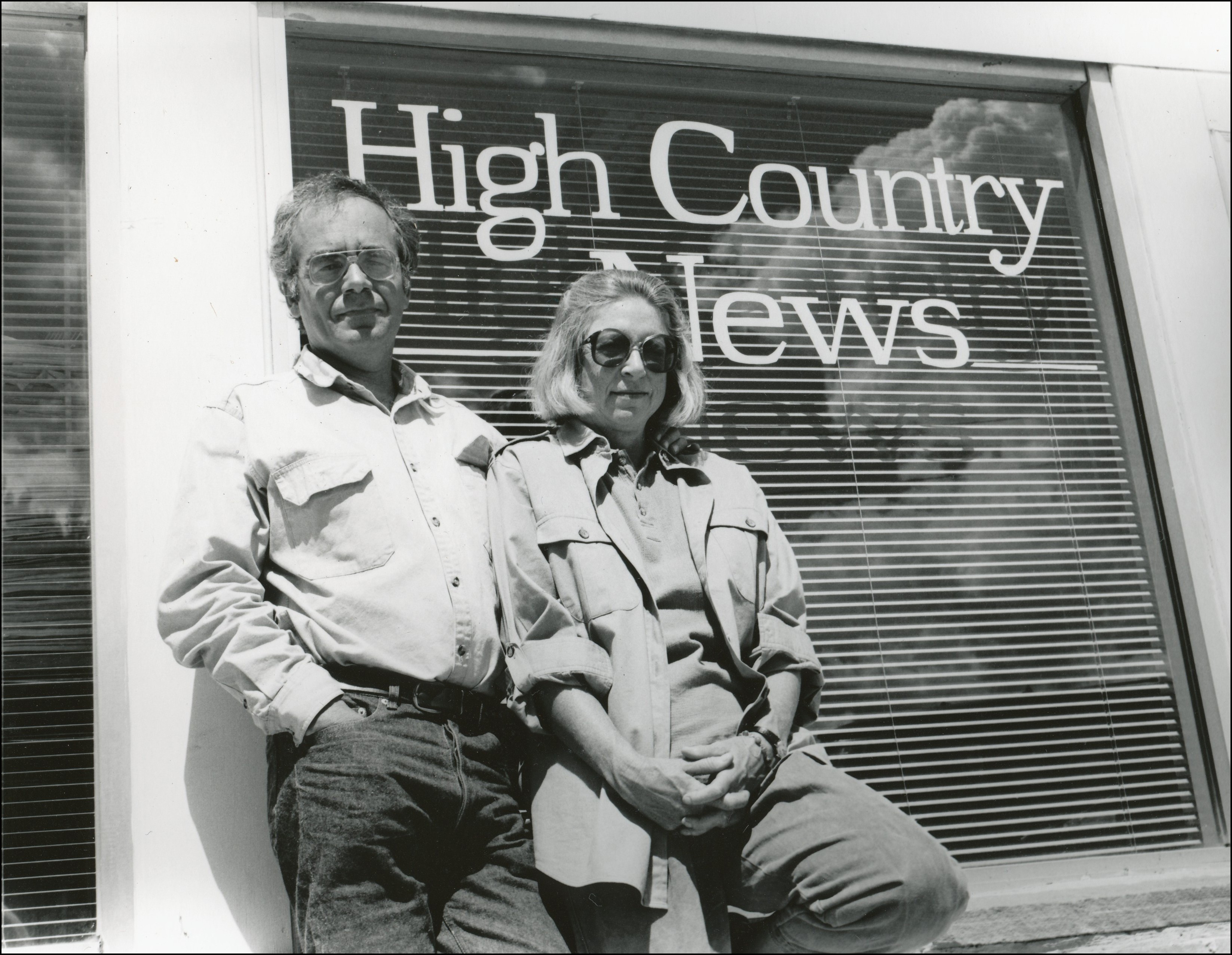 Couple standing in front of window that says High Country News