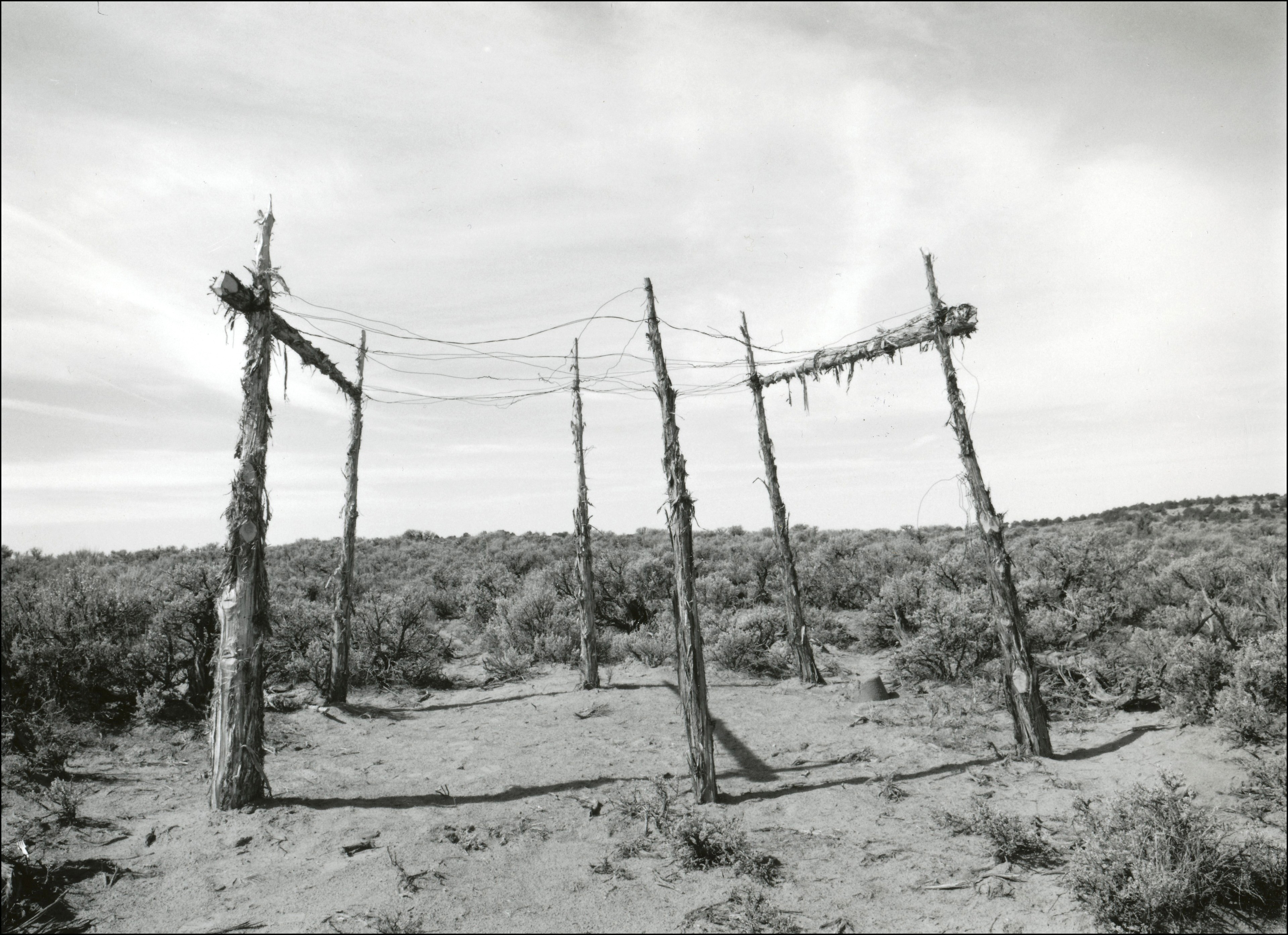 Old structure that has six cedar posts in a circle with wires on top to create some sort of roof. Dirt beneath structure and sagebrush surrounding.