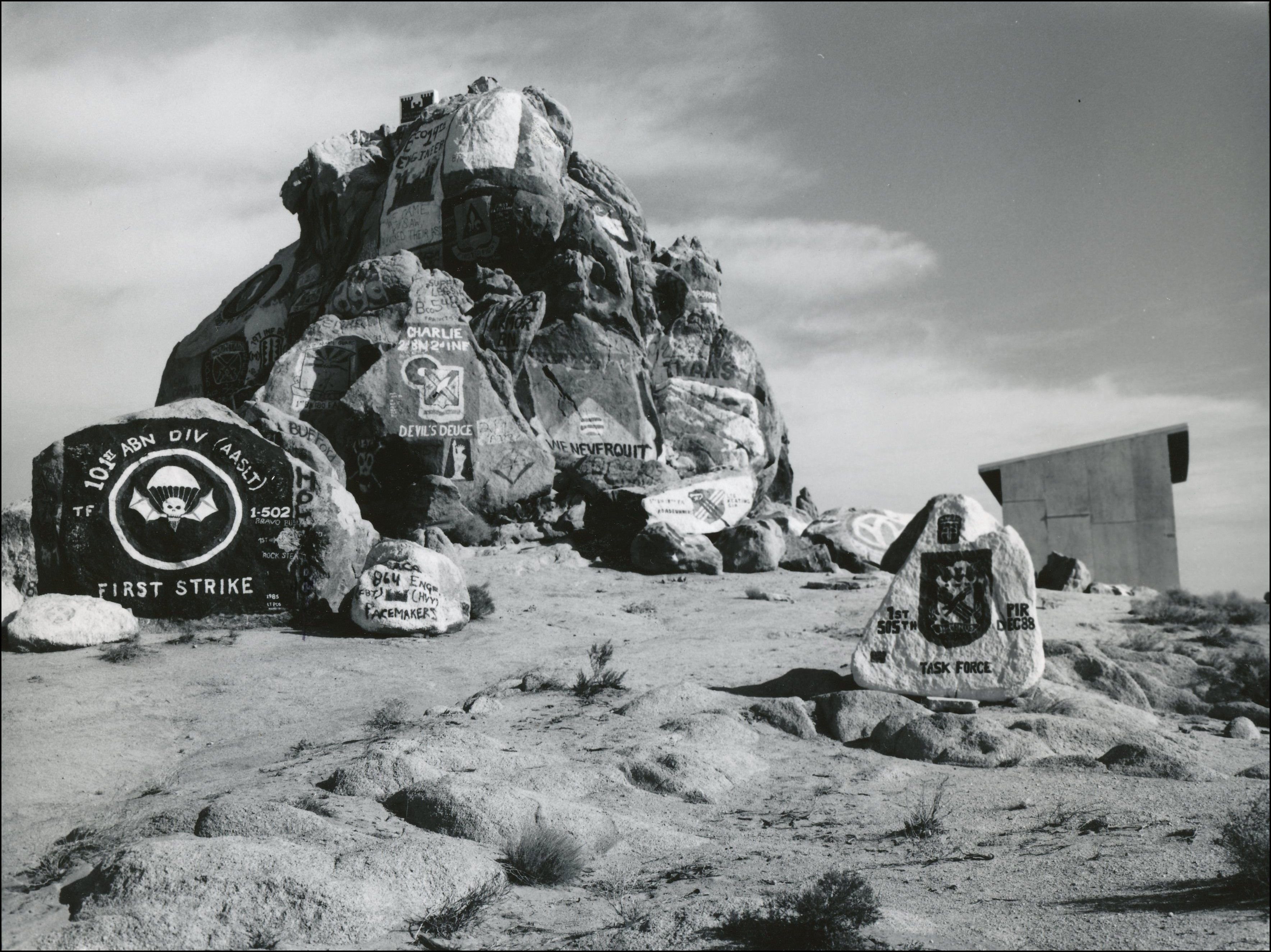 Rock mound and smaller rocks surrounding. Paintings on the rocks of military strikes and other military signage
